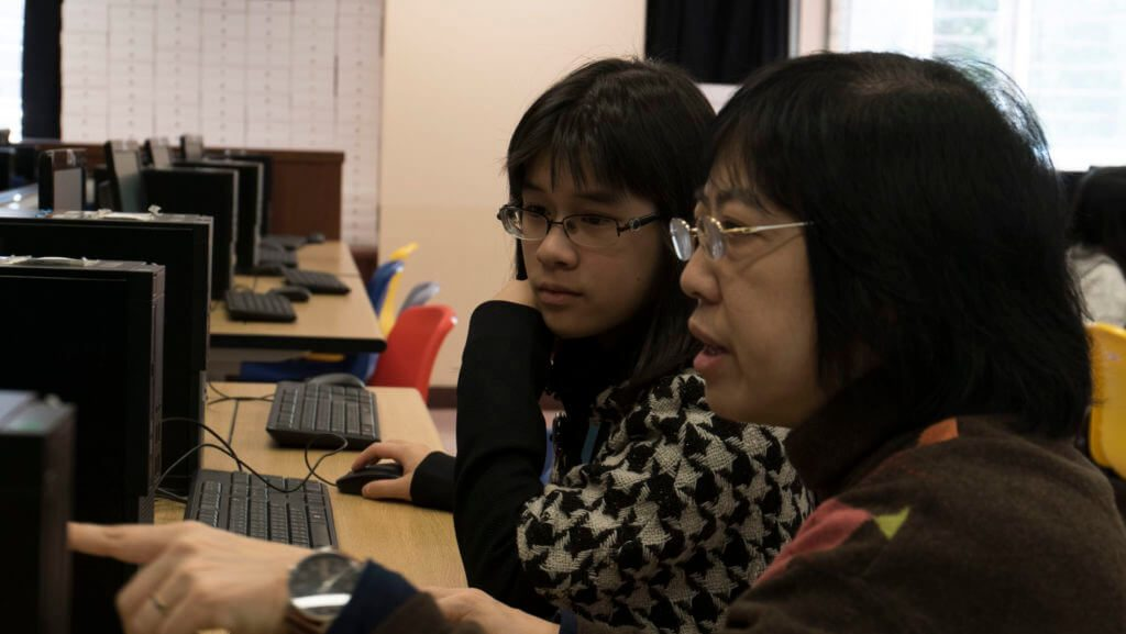 close up photo with a teacher teaching a student in computer room