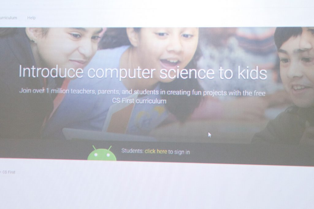 close up photo of two children looking at the computer and smiling