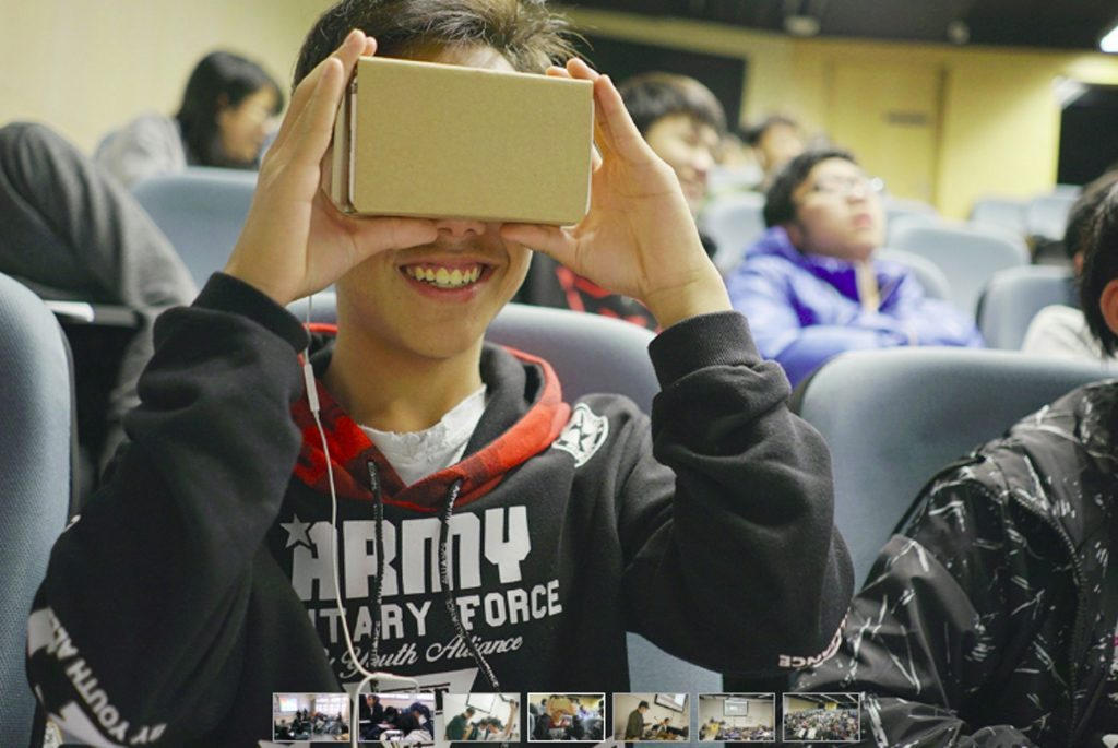a close up photo of a teenager holding a VR cardboard, looking into it with smiling face