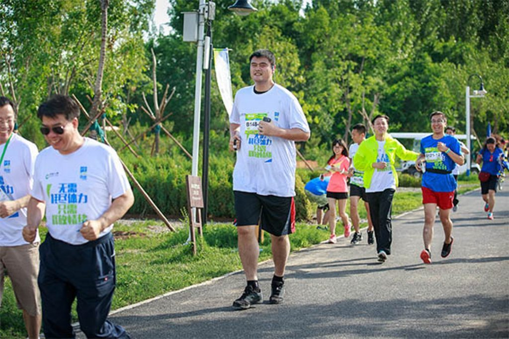 a very tall man running in a charity running event on a sunny day