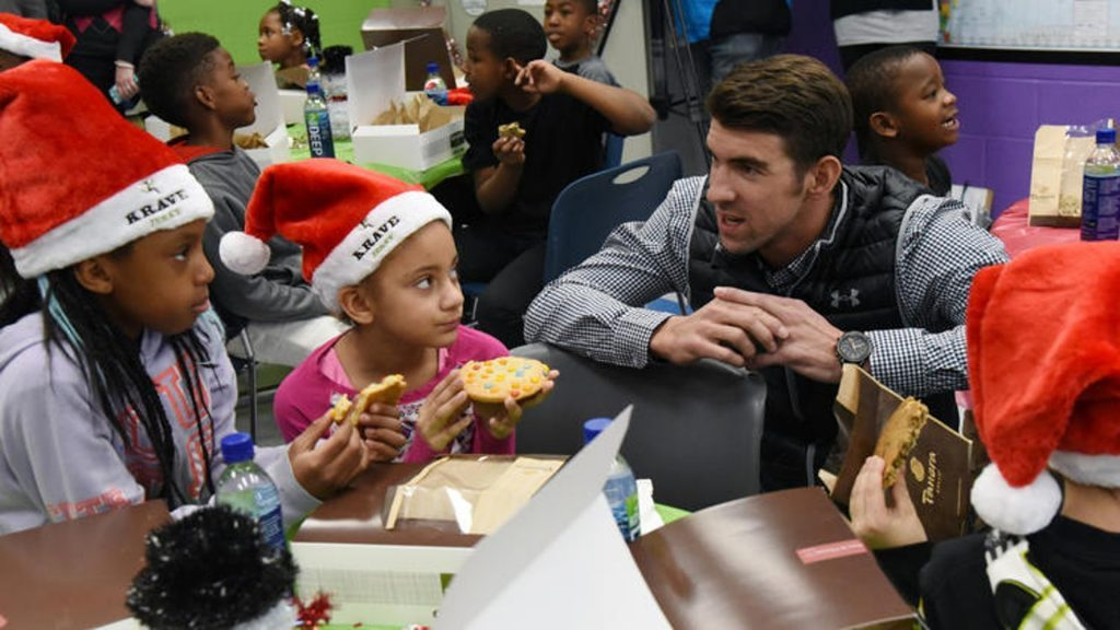 Photo of Michael Phelps talking to a little girl wearing a Christmas hat