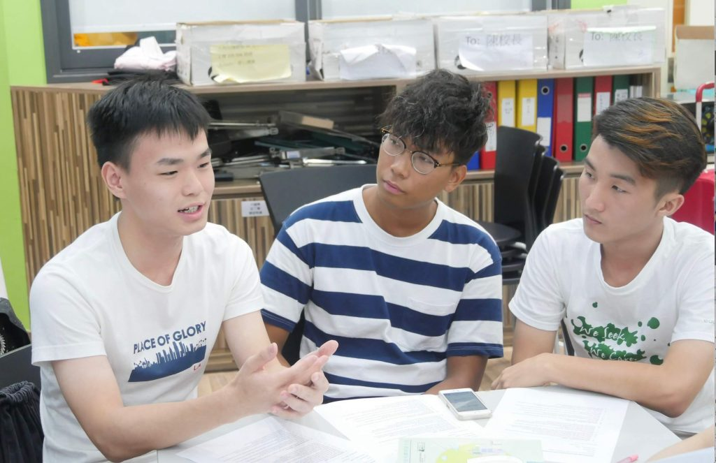 3 young men sit together and talking in a charity centre